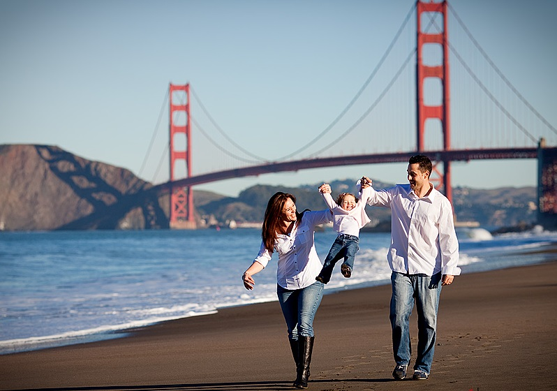 couple with child in front of golden gate bridge