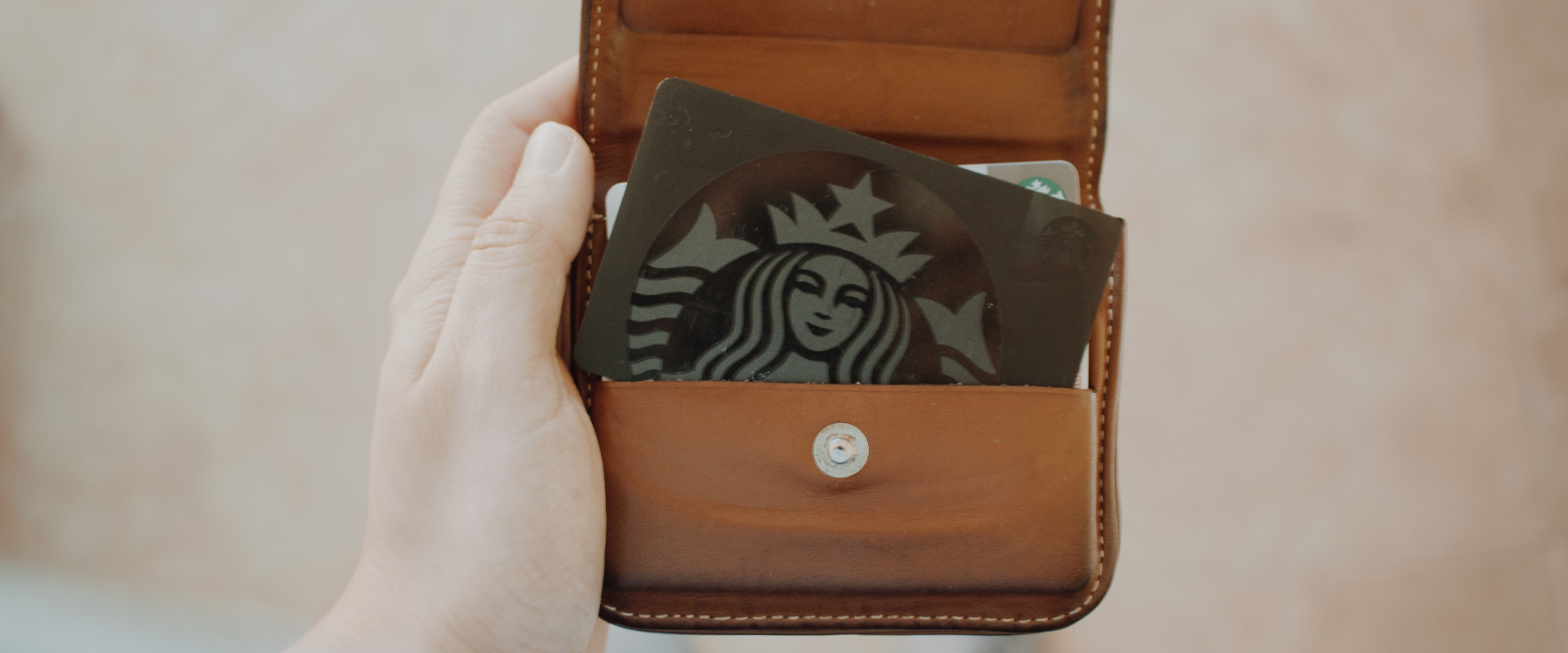 Hand holding pure with Starbucks card