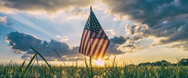 Sunrise behind American flag in Grasslands