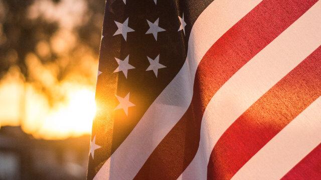 USA Flag at dusk with setting sun